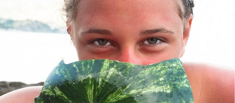 ragazza si nasconde il viso dietro anguria, vediamo solo gli occhi