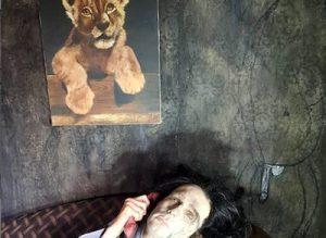 una donna sdraiata a terra morta con in mano una cornetta telefonica rossa e affiancara da un quadro di un leoncino