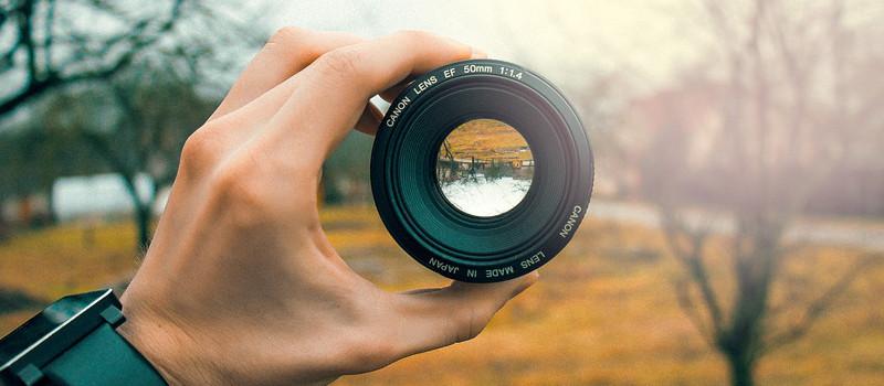 mano regge obiettivo macchina fotografica