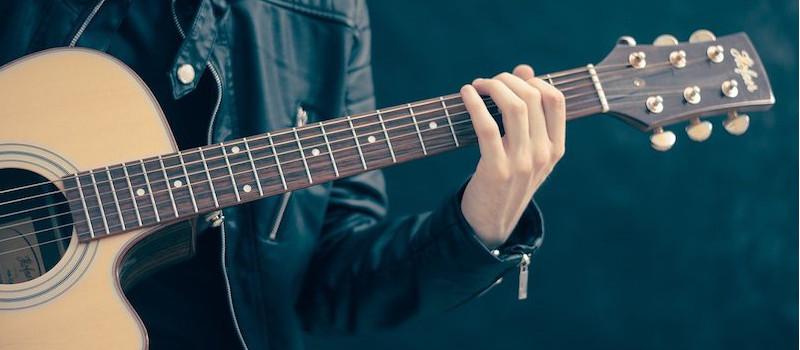 ragazzo-con-giacca-di-pelle-suona-chitarra-in-primo-piano