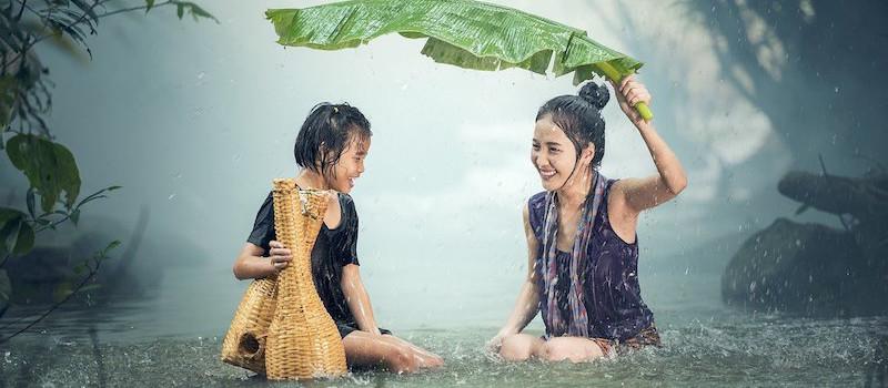 due ragazze fanno il bagno sotto la pioggia